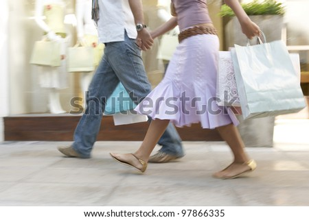 Couple walking down a shopping street with shopping bags, holding hands with motion blur