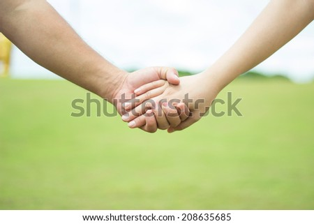Couple walking hand in hand - stock photo