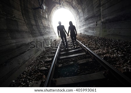 Couple walking hand in hand along the track through a railway tunnel towards the bright light at the other end, they appear as silhouettes against the light