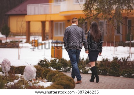 Couple walking hand in hand in a park - stock photo
