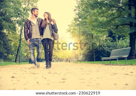 Couple walking hand in hand in a park - Romantic date outdoors - stock photo