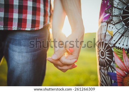 Couple walking holding hands in a park - Romantic date outdoors - stock photo