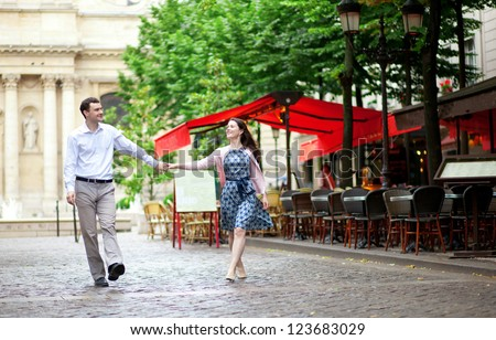 Couple walking in Paris near an outdoor cafe - stock photo