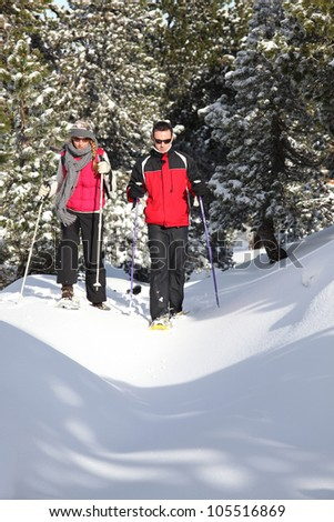 Couple walking in snowshoes - stock photo