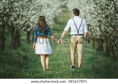 Couple walking in the spring garden, holding their hands. Love concept. Engagement photo session