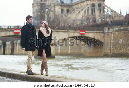Couple walking near the Notre-Dame in Paris - stock photo