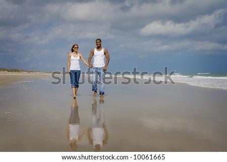 Couple walking on a beach - stock photo