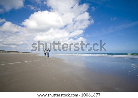 Couple walking on a beach - stock photo