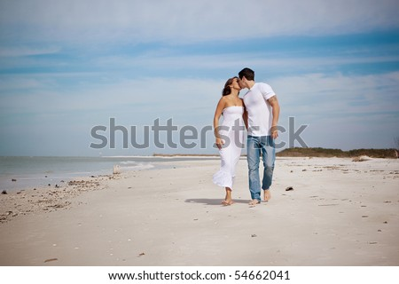 Couple walking on a beach, kissing - stock photo