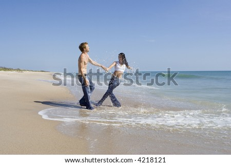 Couple walking on a beach, splashing each other