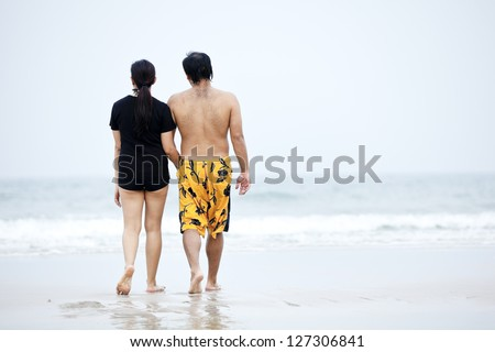 Couple walking on beach - stock photo