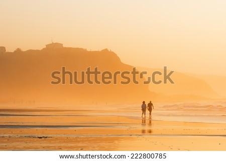 couple walking on beach at sunset. Sopelana - stock photo