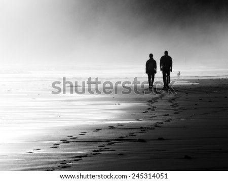 couple walking on beach. Black and white