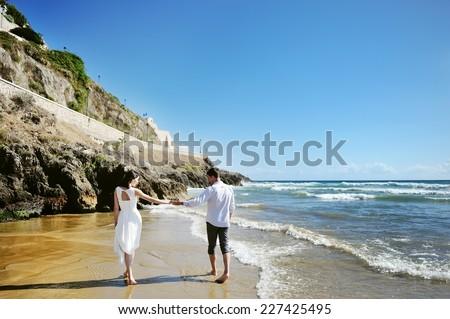 Couple walking on beach together holding hands, Sperlonga, Italy - stock photo