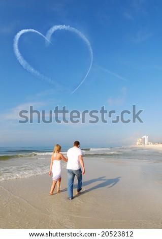 Couple walking on beach under heart skywriting - stock photo