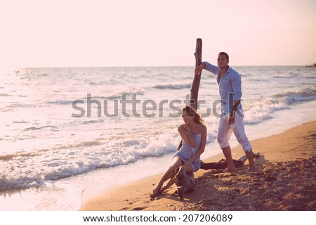 Couple walking on beach. Young happy interracial couple walking on beach smiling holding around each other - stock photo