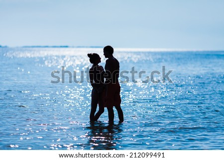 Couple walking on beach. Young happy interracial couple walking on beach smiling holding around each other. Asian woman, Caucasian man. - stock photo