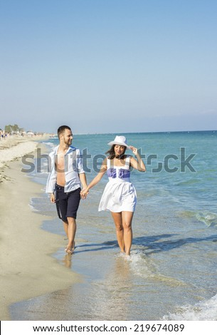 Couple walking on beach. Young happy interracial couple walking on beach smiling holding around each other. Caucasian man and women. - stock photo
