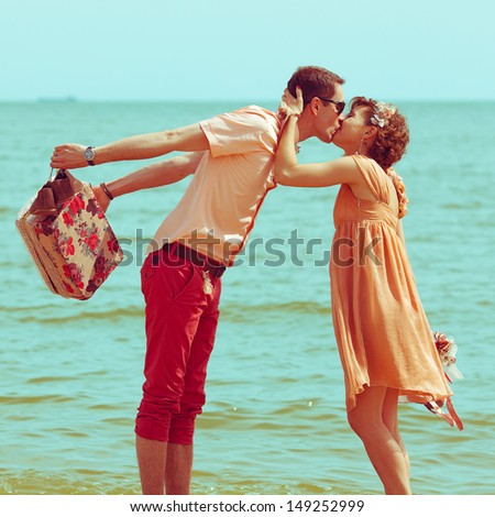 Couple walking on beach. Young happy married hipsters in trendy clothes kissing on beach and holding their shoes. Sunny summer day. Vintage style. Outdoor shot - stock photo