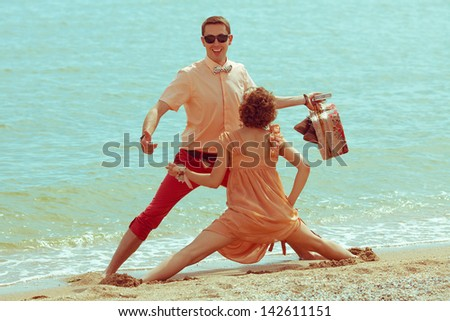 Couple walking on beach. Young happy married hipsters in trendy clothes playing and laughing on beach and holding their shoes and vintage suitcase. Sunny summer day. Outdoor shot - stock photo