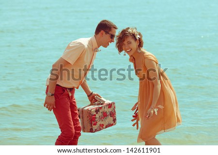 Couple walking on beach. Young happy married hipsters in trendy clothes playing and laughing on beach and holding vintage suitcase. Sunny summer day. Outdoor shot