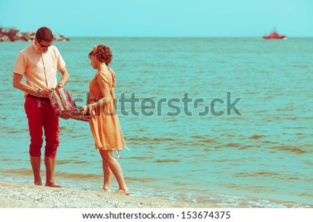 Couple walking on beach. Young happy married hipsters in trendy clothes talking on beach and holding their shoes. Sunny summer day. Copy-space. Outdoor shot - stock photo