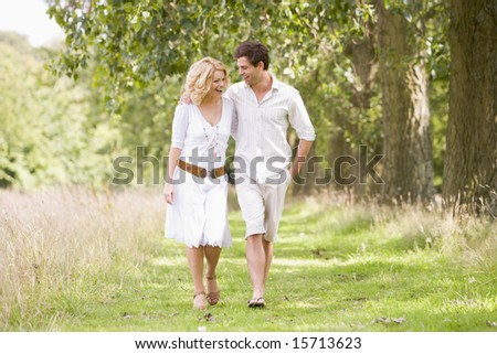 Couple walking on path smiling - stock photo