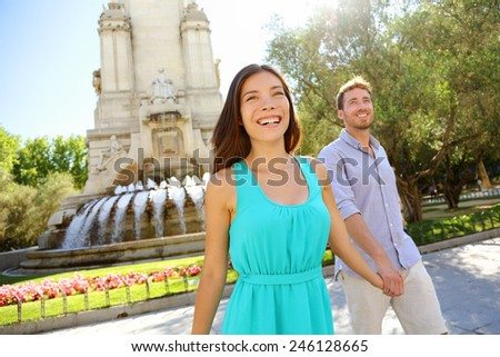 Couple walking on Plaza de Espana Madrid a popular tourist destination landmark. Romantic couple visiting Spanish tourists attractions sightseeing in Madrid, Spain. Asian woman, Caucasian man. - stock photo