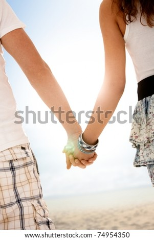 Couple walking on summer beach hand in hand, backlit by sun, focus on hands.? - stock photo