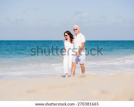 Couple walking on the beach - stock photo