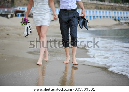 Couple walking on the beach after wedding ceremony