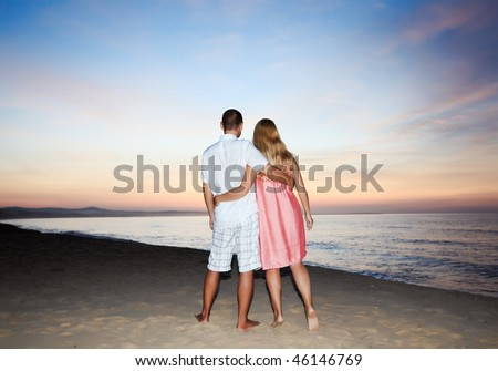 Couple walking on the beach at sunrise time. - stock photo