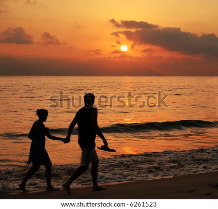 Couple walking on the beach at sunset with some motion blur - stock photo