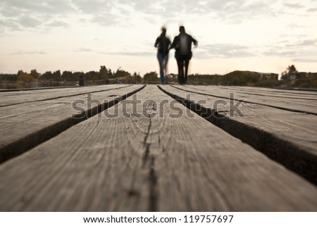 couple walking on the pontoon against the sunset sky