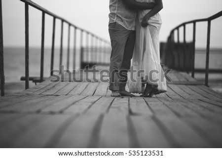 Couple walking seaside, love story concept near sea, walking and holding each others hands,  white and black