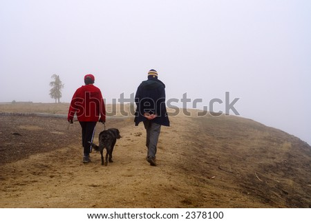 Couple walking the dog in the fog - stock photo