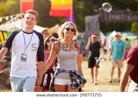 Couple walking through music festival - stock photo