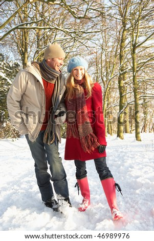 Couple Walking Through Snowy Woodland - stock photo