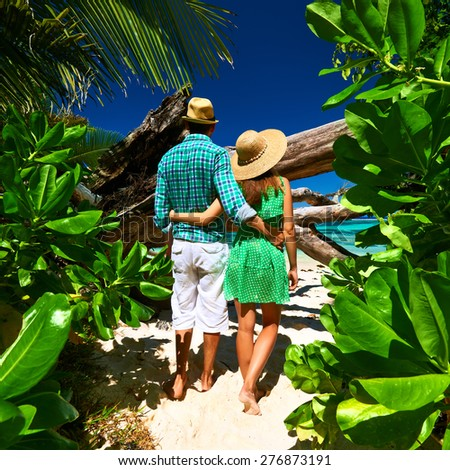 Couple walking to the beach Anse Source d'Argent among tropical foliage at Seychelles, La Digue.  - stock photo