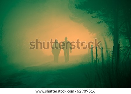 Couple walking trough a foggy forest - stock photo
