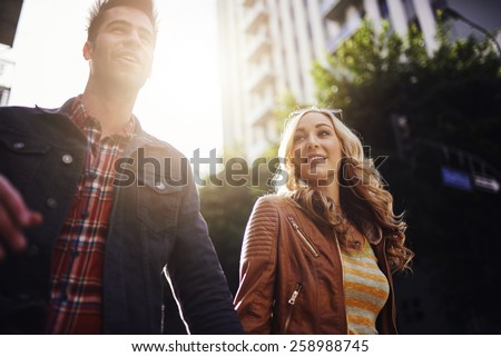 couple walking while holding hands in los angeles with lens flare and selective focus - stock photo