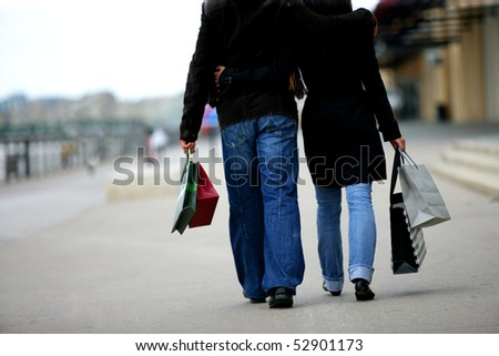 Couple walking with bags - stock photo