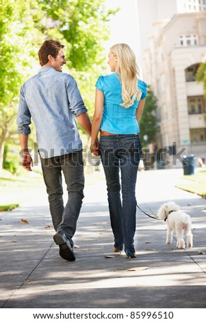 Couple walking with dog in city street - stock photo