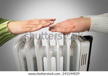 couple warm up hands over electric heater  - stock photo