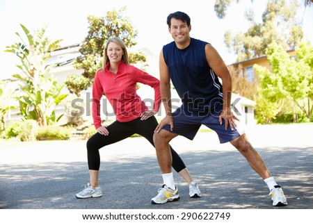 Couple warming up for a run - stock photo