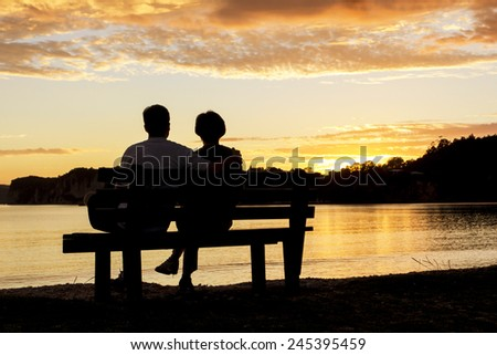 Couple watching a beautiful sunset together - stock photo