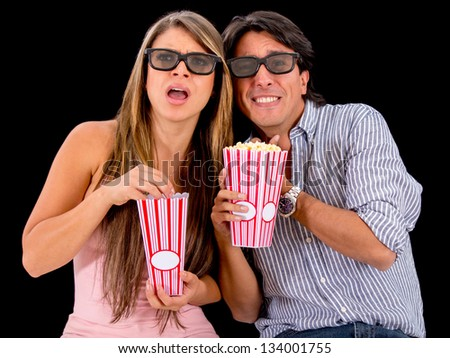 Couple watching a scary 3D movie and wearing glasses