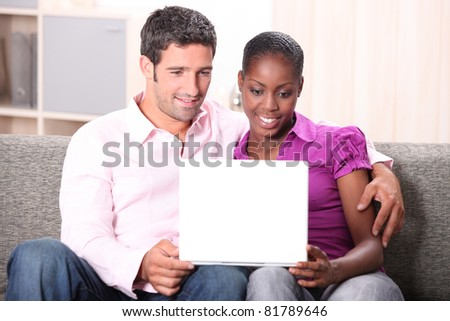 Couple watching laptop screen - stock photo
