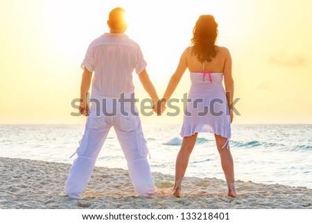Couple watching romantic sunrise on the beach - stock photo