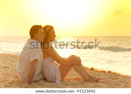 Couple watching romantic sunrise on the beach - stock photo